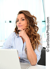 Office worker with thoughtful look in front of laptop computer