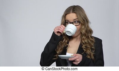 Office worker woman drinking coffee and smiling talking with someone