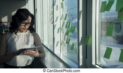 office worker woman looking to tablet, stickers pasted on window