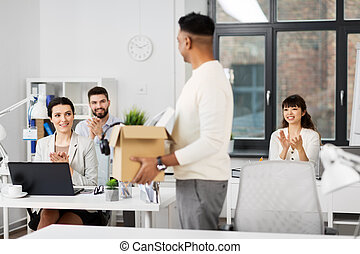 office workers applauding to male colleague