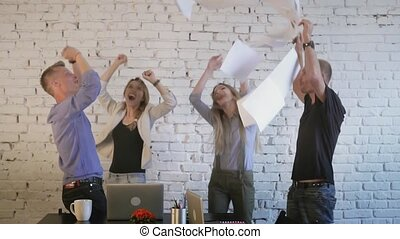 Office workers celebrate victory, dance, throw up paper and...