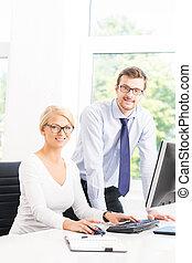 Office workers in formalwear working using computers