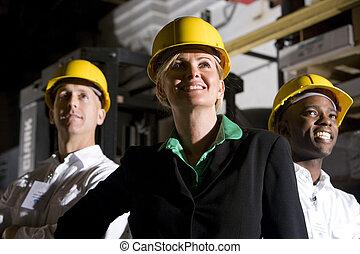 Office workers in storage warehouse wearing hard hats -...