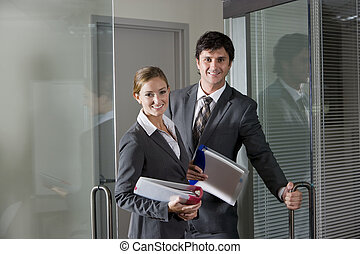 Office workers opening boardroom door - Two office workers...