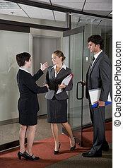 Office workers shaking hands at door of boardroom