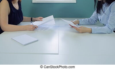 Office workers sitting opposite each other working with documents