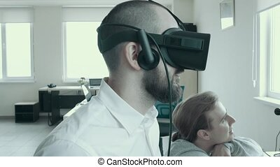 Office workers use virtual reality glasses at work. Close-up of a bald young man in virtual glasses on the background of his colleague.
