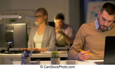 office workers with laptop working at night - business,...