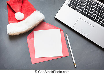 Office workplace with laptop, Santa's cap, accessories on gray background. Top view, copy space.