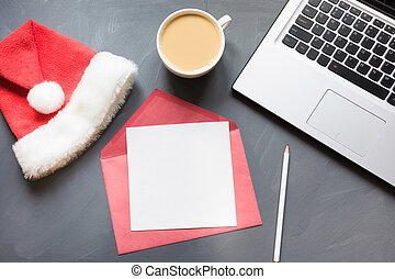 Office workplace with laptop, Santa's cap, cup of coffee, accessories on gray background. Top view with copy space.