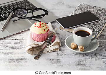 Coffee cup and muffin on table with computer