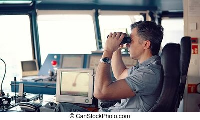 Officer during navigational watch looking through binoculars...