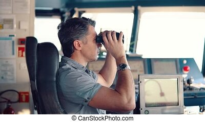 Navigational officer lookout on navigation watch looking through binoculars. Marine industry. COLREG collision regulations