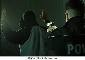 Officer keeping gun on crook