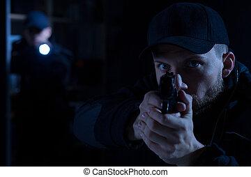 Officer pointing gun at criminal