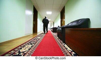Official walking away along office corridor