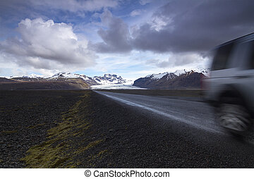 Offroad car on a straight road from the mountains