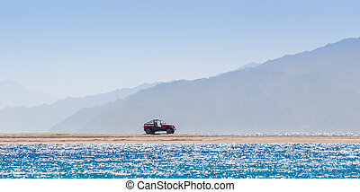 offroad car on an island in the Red Sea against the backdrop of high cliffs in Egypt