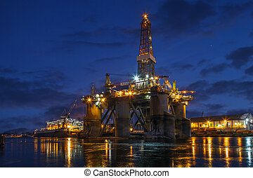 Oil rig at night in winter scenery.