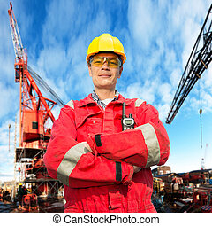 Offshore engineer, looking proudly, standing on the deck of...