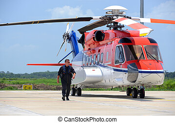 offshore helicopter pilot is walking and smiling beside of...
