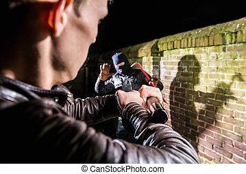 oficial de policía apuntar, antorcha, y, arma de fuego, hacia, busted, espantado, ladrón, por, pared ladrillo, por la noche