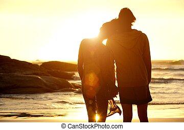 oglądając, para zachód słońca, dzierżawa wręcza, plaża, kochający
