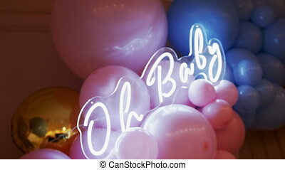 Oh baby text in neon letters on a background of many colorful balloons