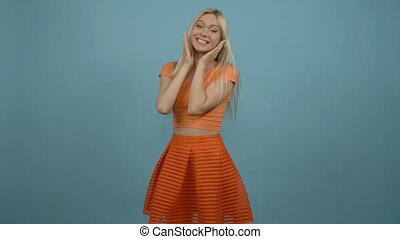 Oh! Beautiful young woman in orange top and skirt keeping hands on chin, looking surprised while standing against blue background