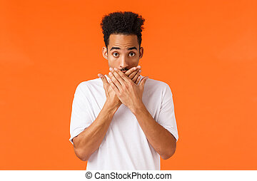 Oh god, what have I done. Embrarrassed or awkward young shocked, speechless african-american male cover mouth and look ashamed, slip tongue, told someones secret, orange background