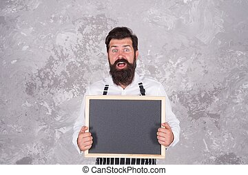 oh my god. bearded man hipster advertising restaurant. professional cook with blackboard. culinary school. brutal guy offer food sales. surprised mature chef holding empty board for copy space