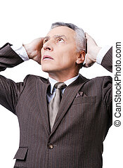 Oh my god! Frustrated mature man in formalwear holding head in hands and looking up while standing against white background