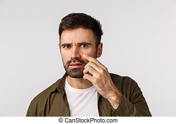 Oh my god is that wrinkle, acne. Frustrated and alarmed displeased handsome bearded man touching his face and examine skin, have bags under eyes, standing white background