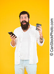 oh my god. mature bearded man chatting on phone while drinking coffee. morning beverage in paper cup. modern life. surprised guy with moustache and beard drink coffee holding smartphone