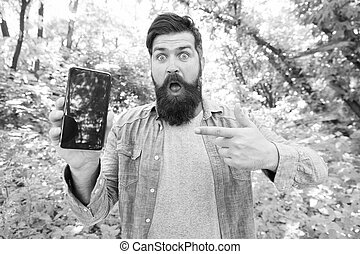 oh my god. surprised bearded man pointing finger on phone. Mature hipster with beard. got lost in forest. brutal man with phone. hipster style. guy in forest use gps navigation. summer camping