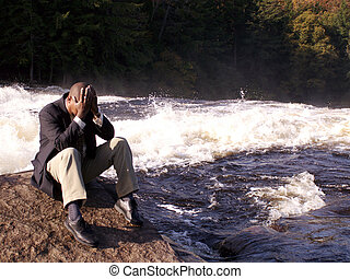 business man in a suit sitting on a rock with hands on head looking overwhelmed