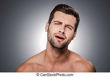 Oh no! Portrait of frustrated young shirtless man looking at camera and grimacing while standing against grey background