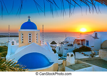 Picturesque view, Old Town of Oia or Ia on the island Santorini, white houses and church with blue domes at sunset, Greece