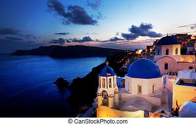 Oia town on Santorini island, Greece at night. Rocks on...
