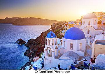 Oia town on Santorini island, Greece at sunset. Rocks on...