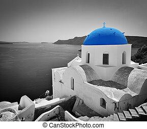 Oia town on Santorini island, Greece. Blue dome church, black and white.