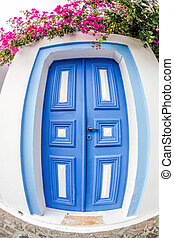 Oia village with typical old blue door on Santorini island in Greece