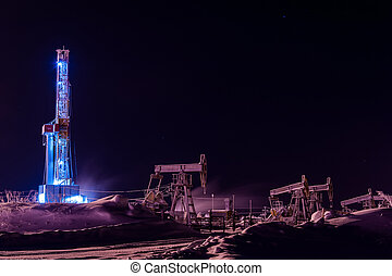 Oil and Gas Drilling Rig at night. Drilling rig and pump jack operation on the oil platform.