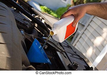 Oil Change - A backyard mechanic pours motor oil into the...