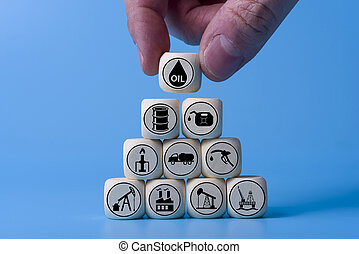 Oil concept with icons on wooden cubes, blue background.