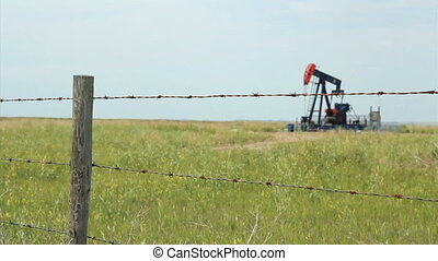 Oil Derrick Behind Wire Fence - A lonely oil pump works...