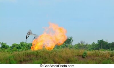 Oil derrick stands in the middle of green nature. Strong flames burst from the ground.