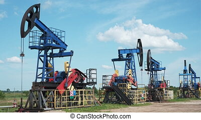 Row of modern pumps extracting oil from wells against cloudy sky in field in countryside