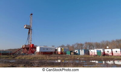 Oil drilling rig in field after rain