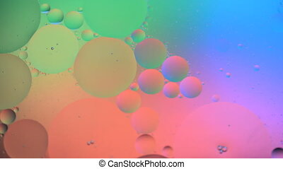 Oil drops moving in water. Abstract background with colorful gradient colors. Macro shooting. DOF